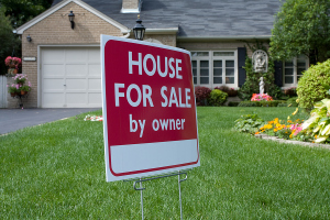 For Sale By Owner (FSBO) sign in front of real estate listing